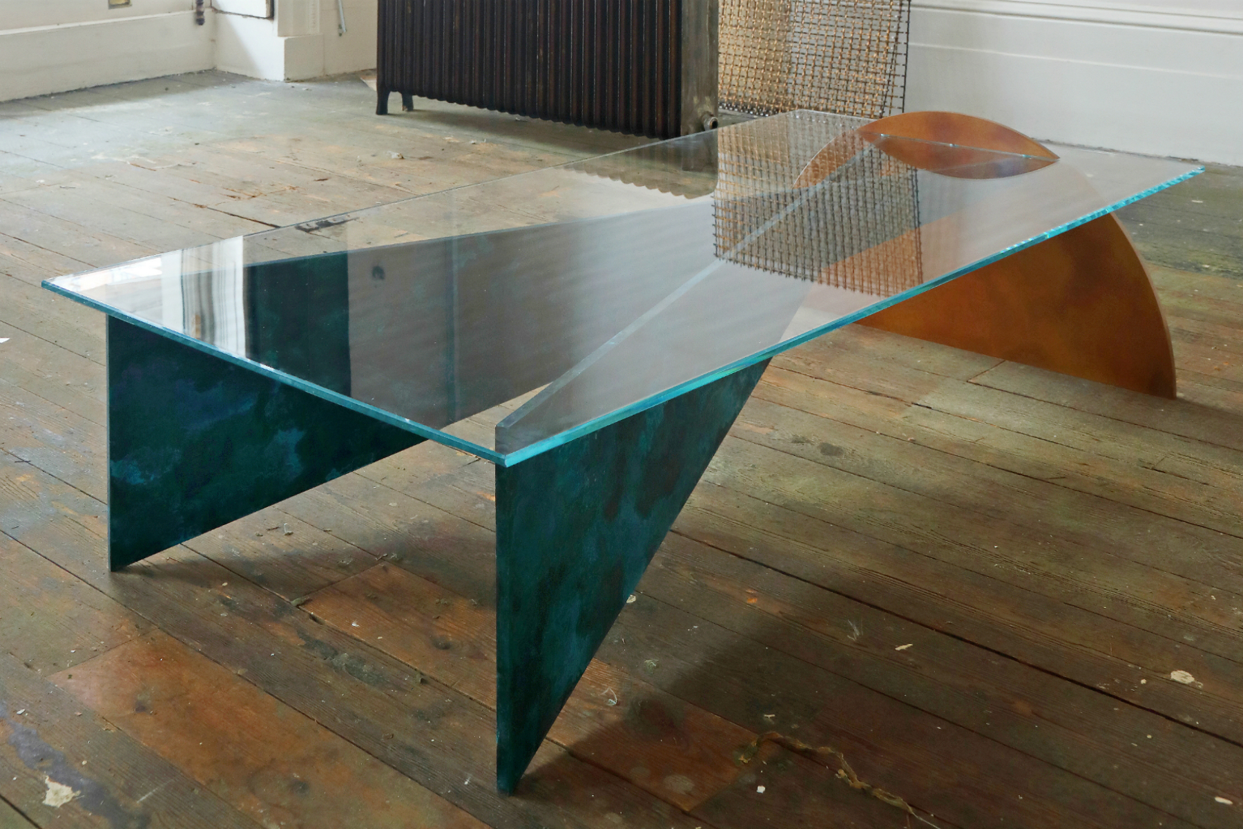 Thonis Table designed by Studioloop. Geometric shapes slot together to form the table structure, with low iron glass top. Patinated finishes